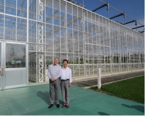 Photo of Zu and Goodman standing in front of greenhouse